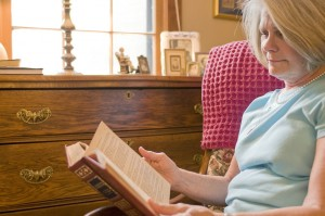 Old woman reading in her home living independently with her TGA mobility scooters